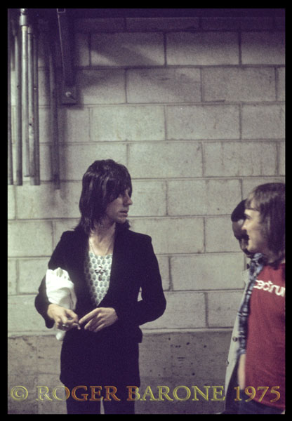 Guitarist Jeff Beck pauses to chat with  Spectrum changeover crew employee Mark Huckle backstage. Jeff Beck and John McLauglin's Mahavishnu Orchestra shared top billing. © ROGER BARONE 1975