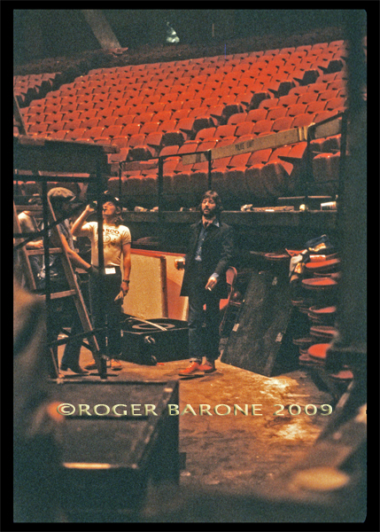 After his Spectrum performance, Eric Clapton watches the roadies and stagehands dismantle the stage. Clapton is pictures with a Heineken beer and cigarette. © roger barone 2009
