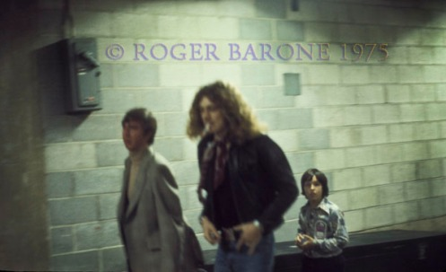 Electric Factory Concerts' promoter Allen Spivak often brought his son along to the shows. Young Adam,   with a backstage pass on his chest, follows Led Zeppelin's Robert Plant to the dressing rooms and production staff offices.© ROGER BARONE 1975
