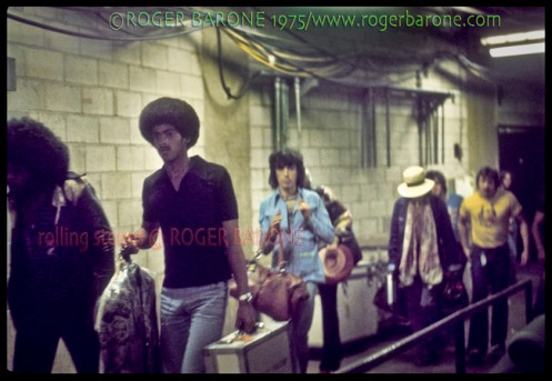 The Rolling Stones backstage at The Spectrum walking to the dressing rooms. From left, Billy Preston, Ollie Brown, BIll Wyman, Ronnie Wood (blocked by Wyman), Keith Richards and two Stones' assistants. © ROGER BARONE 1975