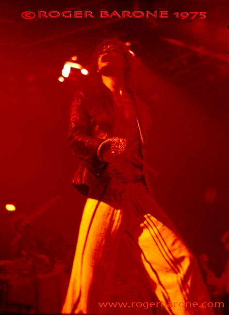 "Mick Jagger is saturated in red lights while singing ""Midnight Rambler"" at the Spectrum. © ROGER BARONE 1975"