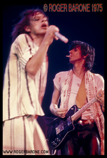 A cigarette dangles from the lips of Keith Richards while Mick Jagger sings into the microphone. © ROGER BARONE 1975
