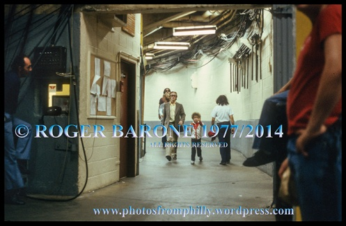 Stephen Stills walking backstage at Spectrum Arena with a young child. © roger barone 1977/2014